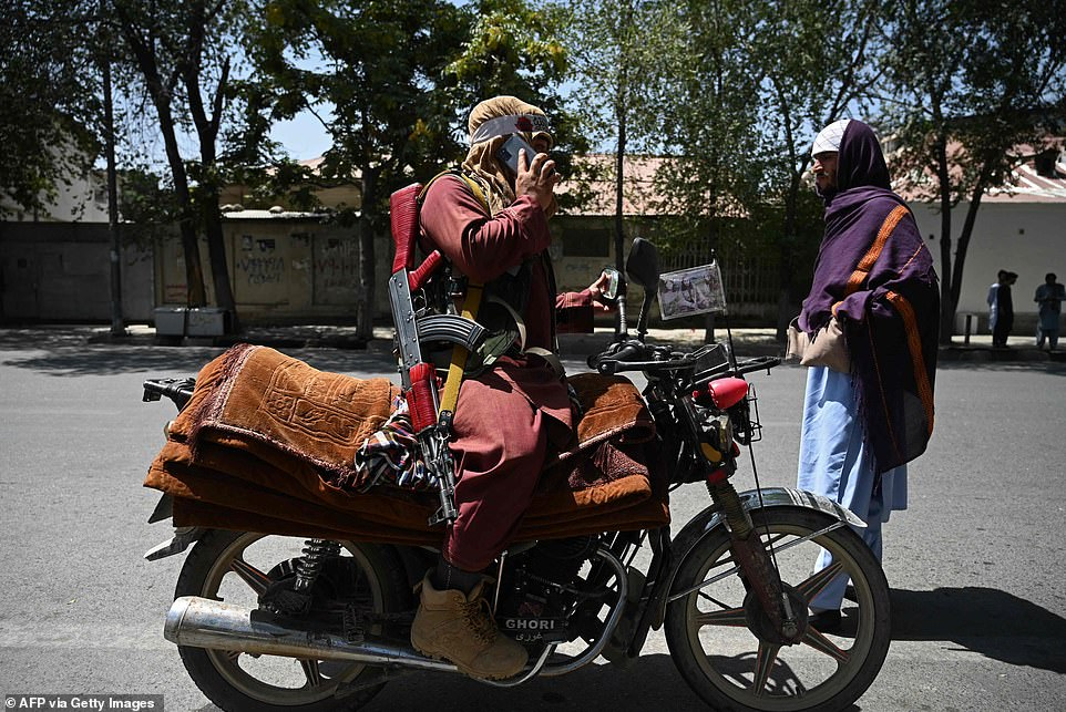 A Taliban fighter sits on his motorcycle along a roadside at Shahr-e Naw in Kabul on August 16, 2021