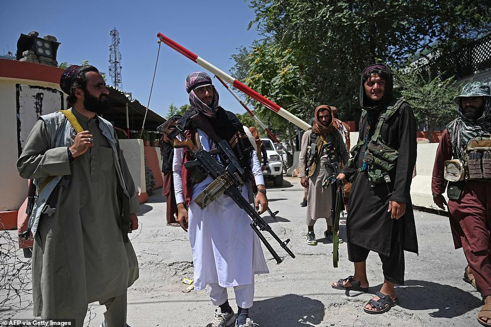 Taliban fighters guard a roadside near the Zanbaq Square in Kabul on Monday after the group swept the capital, forcing President Ashraf Ghani to flee