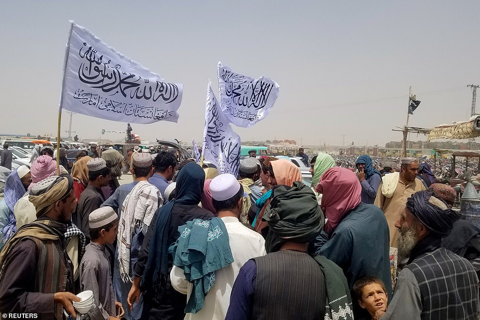 Pictured:People with Taliban's flags gather to welcome a man (not pictured) who was released from prison in Afghanistan, upon his arrival at the Friendship Gate crossing point at the Pakistan-Afghanistan border town of Chaman, Pakistan August 16, 2021