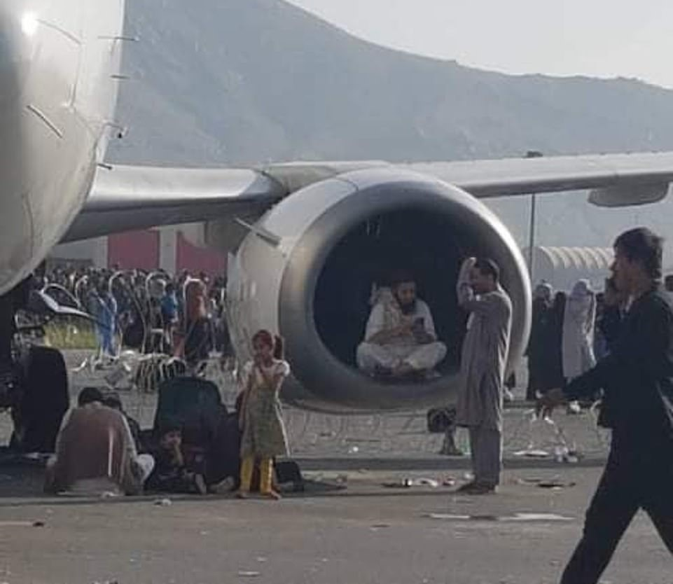 A man sits inside the frame of a airplane engine while waiting for an evacuation flight out of Kabul after the Taliban took the capital on Sunday