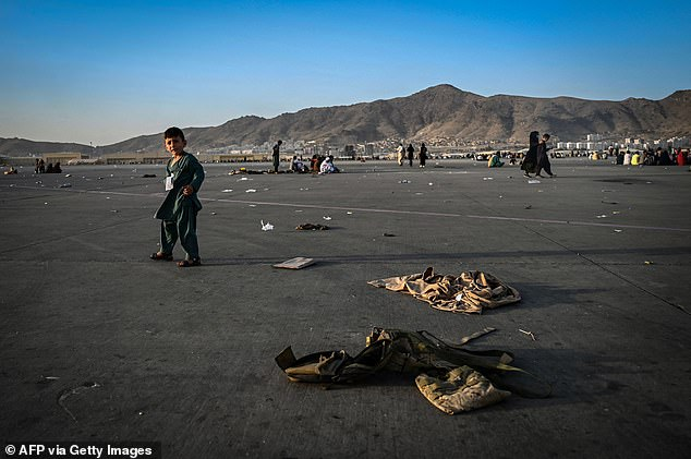 An Afghan child walks near military uniforms as he and elders wait to leave the Kabul airport on August 16th