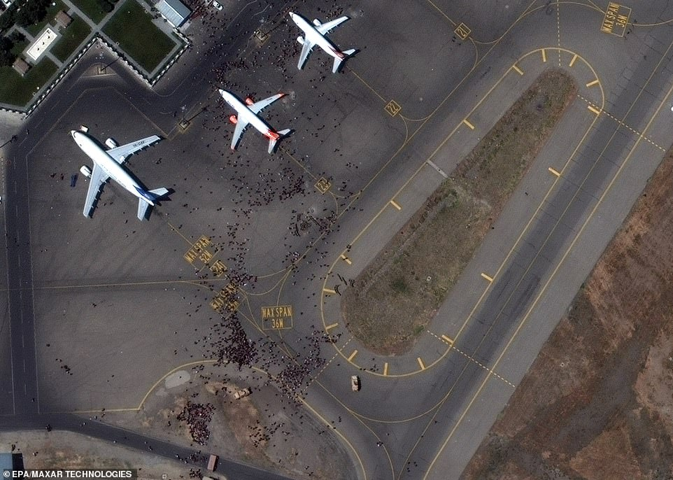 Hundreds of desperate people are seen around grounded planes at Kabul airport in this satellite image