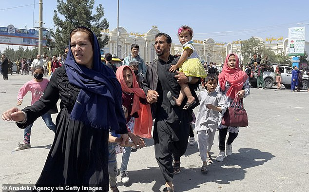 An Afghan family rushes to the Hamid Karzai International Airport as they flee the Afghan capital of Kabul on Monday
