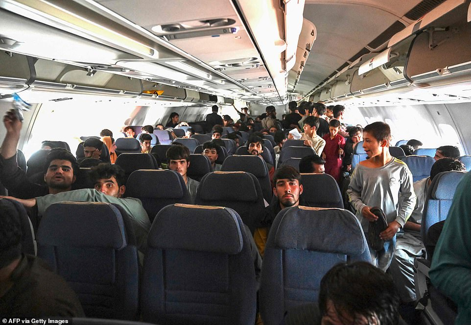 Afghan passengers sit inside a plane as they wait to leave Kabul airport although all commercial flights have been grounded, with only military aircraft being allowed in and out