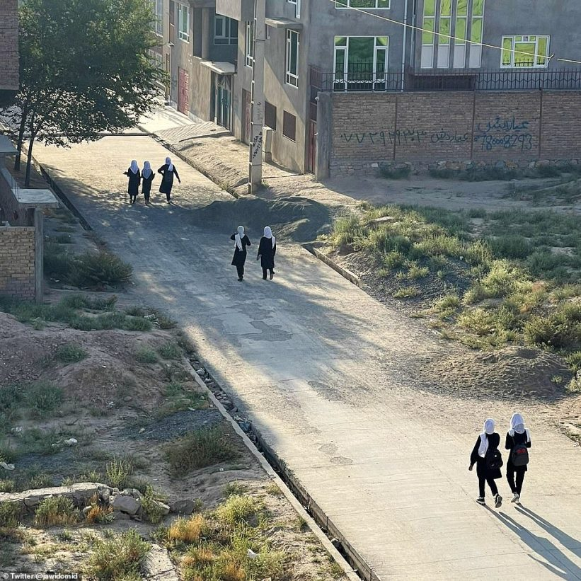Pictured: A street in Kabul on Monday morning reportedly showing girls walking to school in pairs, wearing white head scarfs and black traditional clothing after the Taliban takeover, which has raised fears of a return to the brutal laws last seen under Taliban rule before 2001