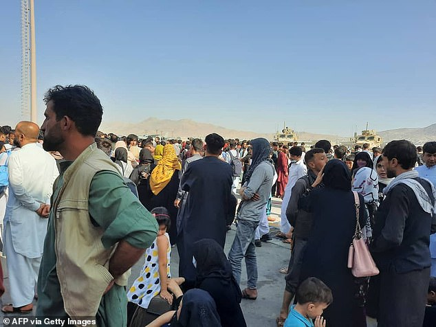 Afghans crowd on to the apron at Kabul airport as they try to flee the country