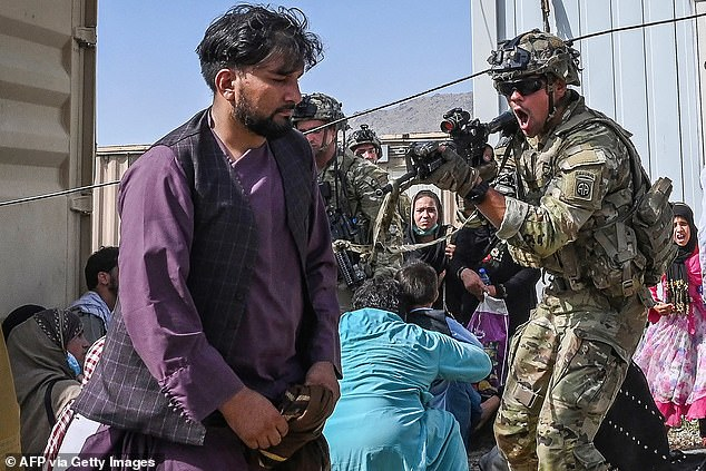 Veterans and their families are speaking out in wake of the US military's withdrawal from Afghanistan (pictured: US soldier pointing his gun towards an Afghan passenger at the Kabul airport in Kabul on Monday)