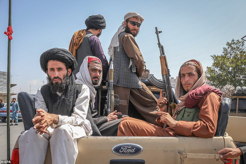 Taliban fighters are seen on the back of a vehicle in Kabul, Afghanistan, August 16, 2021