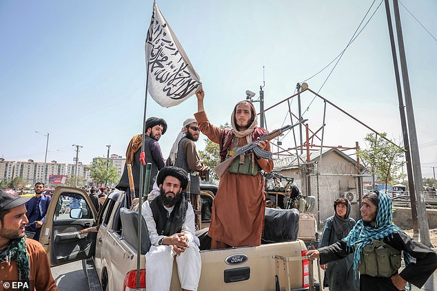 Taliban fighters are seen on the back of a vehicle patrolling Kabul on Monday