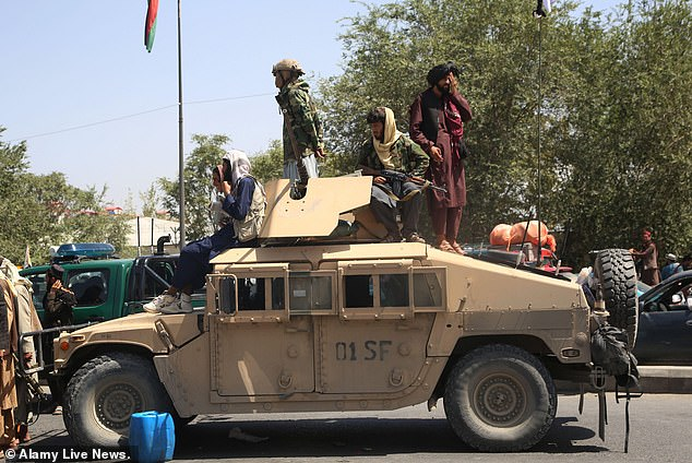 Afghan Taliban fighters are seen on a US-made military vehicle in Kabul on Monday