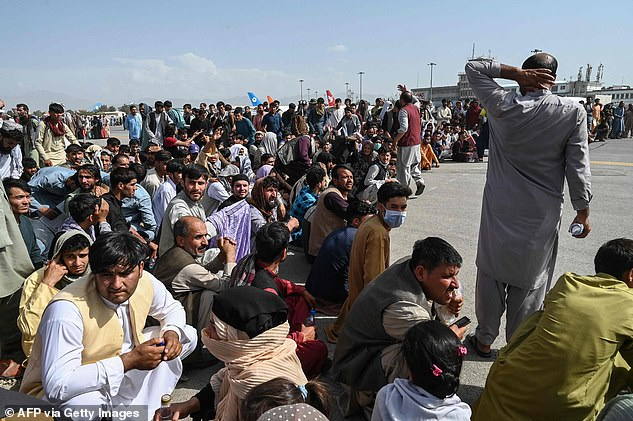 Afghan passengers sit as they wait to leave the Kabul airport in Kabul on Monday, after a stunningly swift end to Afghanistan's 20-year war