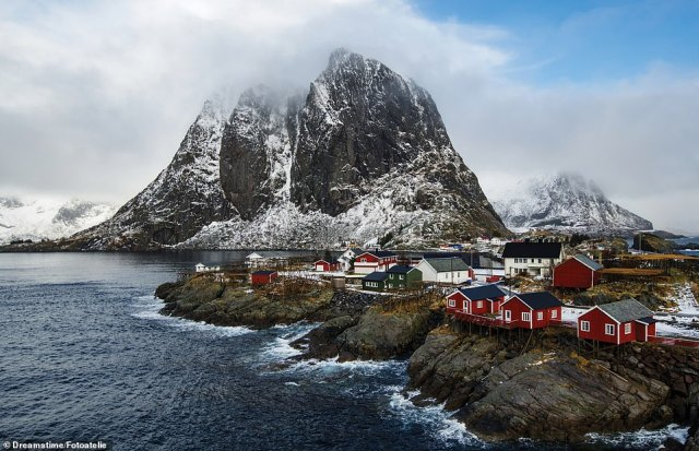 HAMNOY, LOFOTEN ISLANDS, NORWAY, The fishing hamlet of Hamnoy is on Moskenesoya, near the southern end of the Lofoten archipelago, which experiences a 'relatively mild climate for its latitude thanks to the Gulf Stream', Martin observes, adding: 'The traditional red Rorbu houses hang over the rocks or water, one end propped on poles, for easy access to boats'