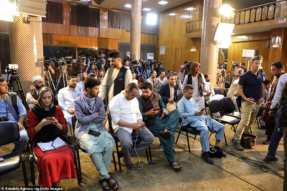 Press members are seen as Taliban spokesperson Zabihullah Mujahid holds a press conference in Kabul