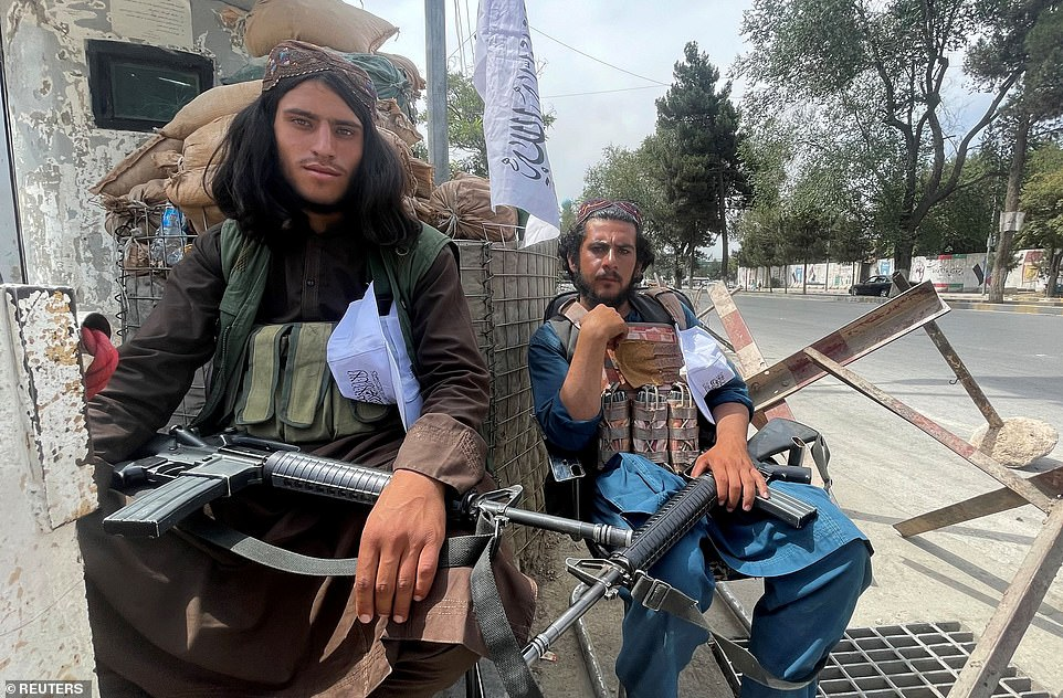 Members of Taliban forces sit at a checkpoint in Kabul, Afghanistan on Tuesday following their takeover of the city