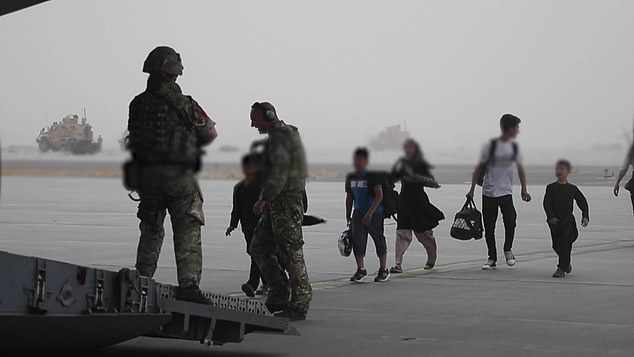 Afghans who apply to come to Britain are being rigorously checked for links with radical Islamist groups and crime. Pictured: Members of the UK Armed Forces help Afghan civilians onto the RAF aircraft in Kabul on Monday