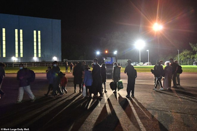 British nationals and Afghan evacuees are seen walking on the tarmac at RAF Brize Norton in Oxfordshire last night