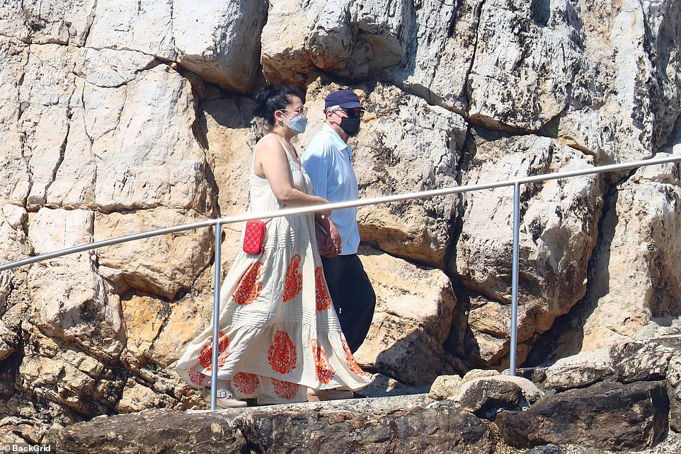 Take my hand: Robert looked happy and relaxed in the company of the woman as they supported each other while climbing down the walkway on a rocky cliff edge