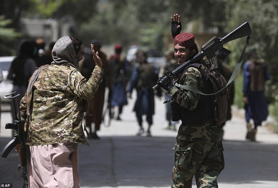 British forces say evacuation flights are happening with 'consent' of the Taliban, as fighters were pictured patrolling one of the main roads to the airport today (pictured)