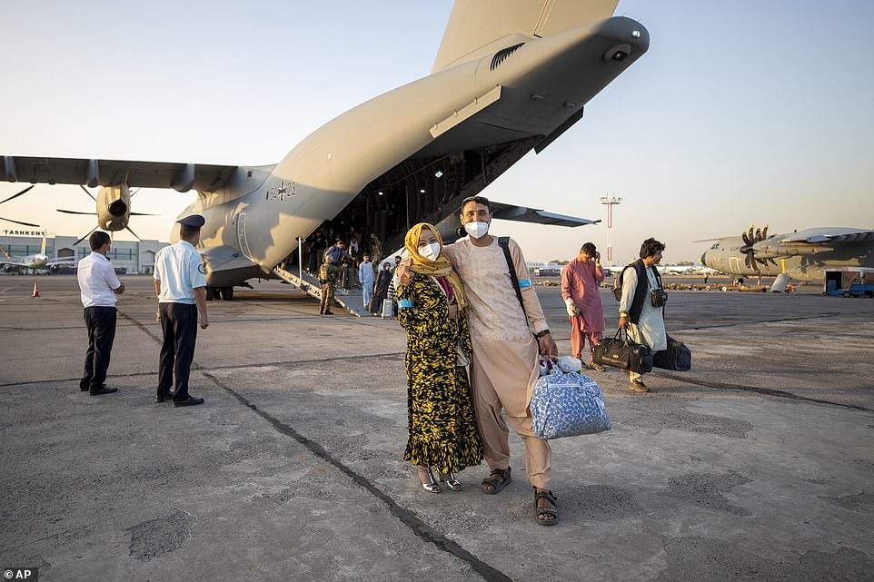 People evacuated from Afghanistan by a German Bundeswehr airplane arrive at the airport in Tashkent, Uzbekistan