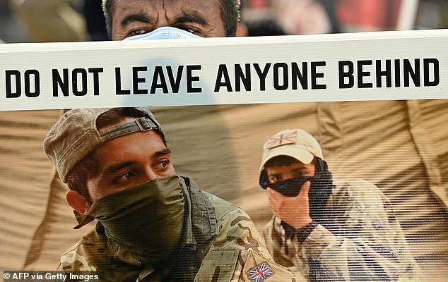 A protester holds up a large banner with British soldiers that reads: 'Do not leave anyone behind'