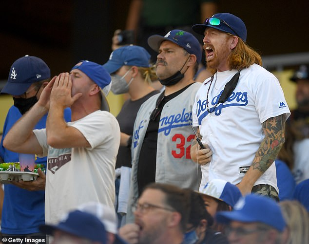 The new mandate, which calls for masks to be worn at outdoor events with more than 10,000 people in attendance, will affect fans at Dodgers Stadium. Pictured, fans cheering on Aug. 3