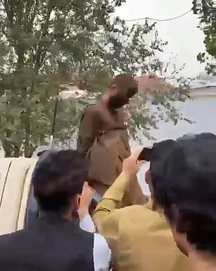 A traffic cop stands nearby and waves through traffic, seemingly unperturbed by the commotion around the accused man.