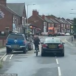 Cyclist crashes onto the road after hitching a ride by hanging onto a passing car 💥👩💥