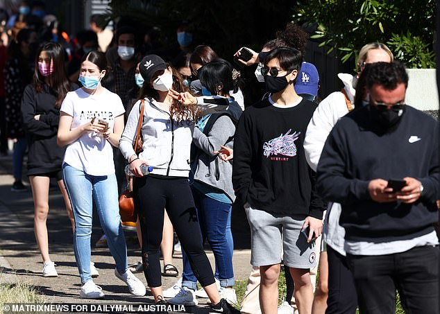A long queue of people is seen lining up to vaccinated against Covid at Bankstown in Sydney on Wednesday (pictured) - with the area suffering a worrying influx of Covid cases