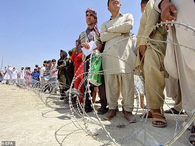 Hundreds of Afghans line up on August 17 around theHamid Karzai International Airport in Kabul in a desperate attempt to try and get on board an evacuation flight out of Afghanistan