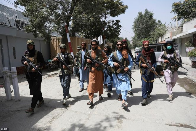 Armed and dangerous: Taliban fighters patrol the streets of Kabul yesterday
