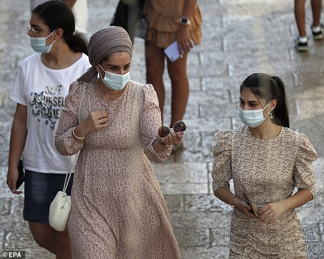 Israeli women are pictured wearing face masks in the street in Jerusalem on Thursday