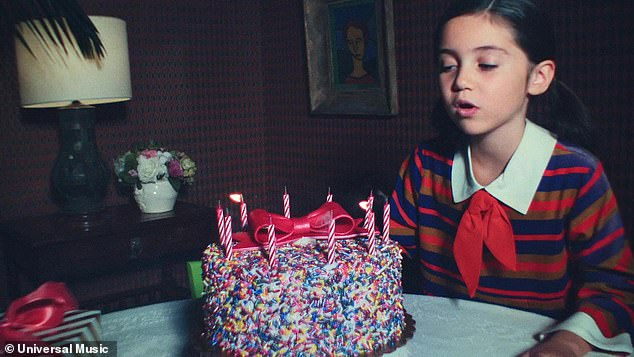 Sweet moment: During the lyric 'Dear little me, I'm sorry that it took so long, But baby, you're free,' the little girl was seen again, blowing out candles on a real birthday cake with sprinkles