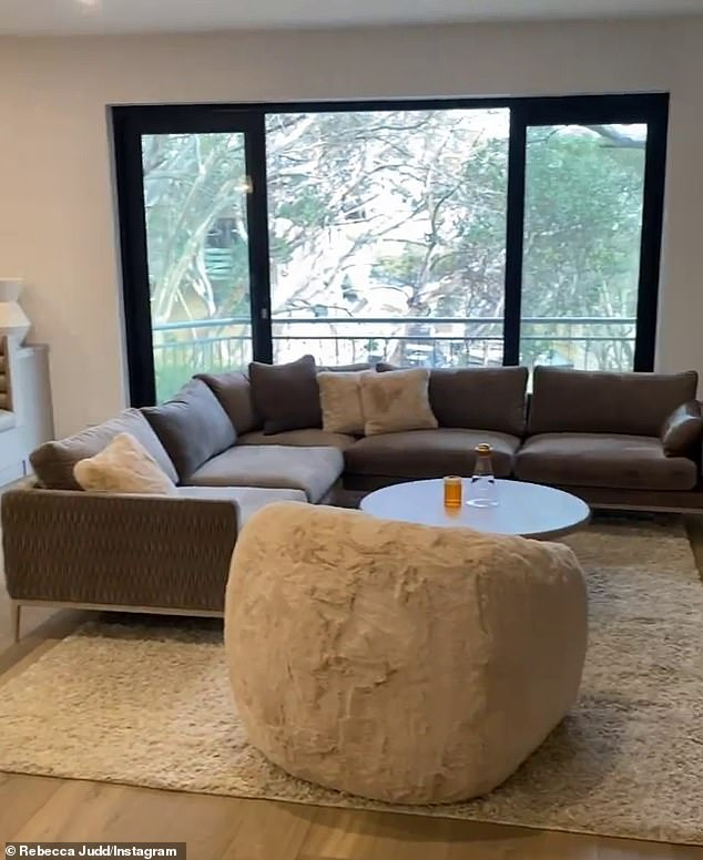 In addition to the large feature wall - decorated with sculptures, books, candles and a fireplace - was a coffee table, a grey L-shape lounge with an off-white fluffy chair