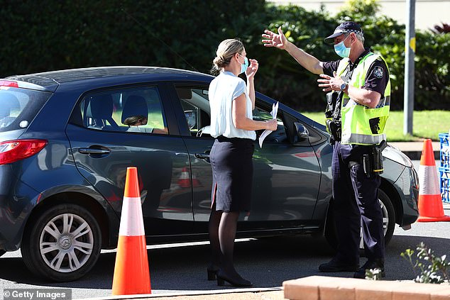 Queensland Police stop vehicles on the border with NSW at Coolangatta. New border measures require essential workers entering Queensland to have had at least one dose of a Covid-19 vaccine