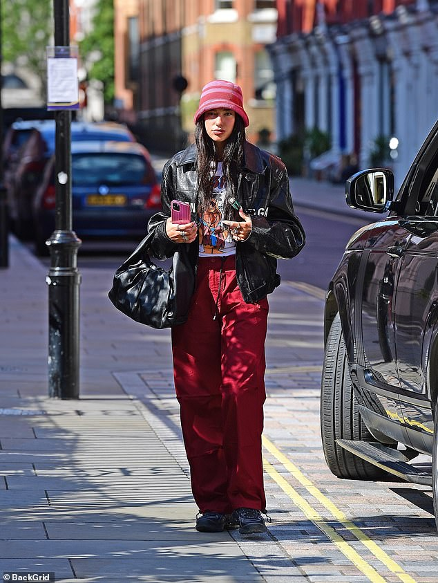 Just touched down in London town: Dua Lipa, 26, showed off her quirky style as she teamed red combats and a biker jacket with a pink hat and orange shades, in London on Wednesday