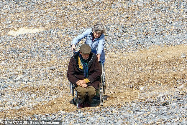 Beach set: In the scenes, the BAFTA award-winning actress was spotted in a dusty blue coat as she wheeled Rupert, 62, in a wheelchair