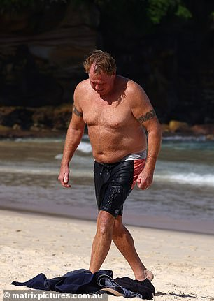 Staring out to sea: After taking a dip in the ocean, Markle was seen chatting on the phone on loud speaker while he had a towel wrapped around his waist