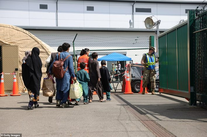 Evacuees from Afghanistan walk from a temporary tent to a bus at Ramstein Air Base on August 26
