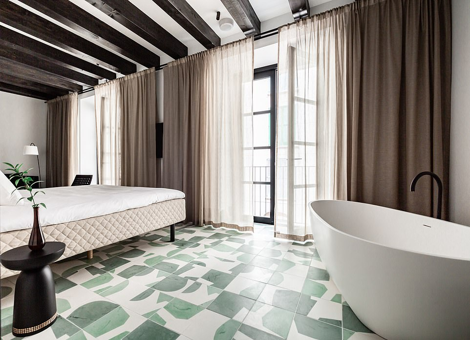 There are beautiful green-and-white handmade watercolour-style tiles running through the bedrooms and public spaces