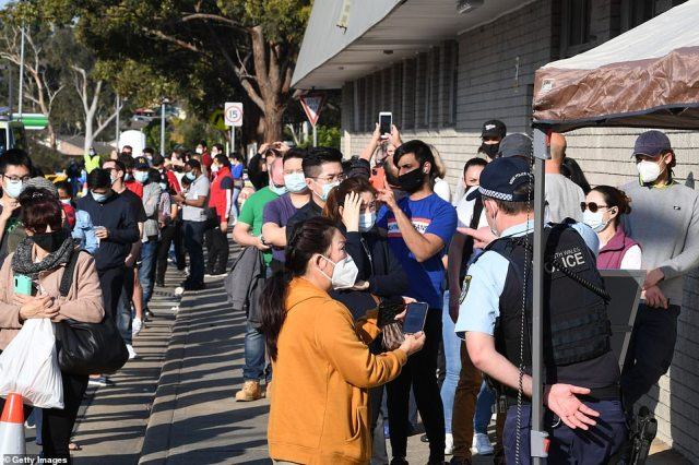 Hundreds of people wait in line for their Covid-19 vaccine at the South Western Sydney vaccination centre at Macquarie Fields