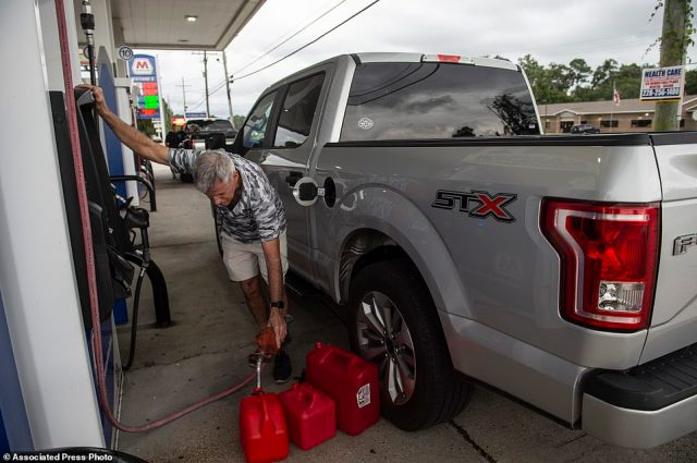 Gary Sullivan, of Gulf Hills, fills extra gas containers at Marathon Gas, Friday, Aug. 27, 2021, in Ocean Springs, Miss., in preparation for Hurricane Ida. (Hannah Ruhoff/The Sun Herald via AP)