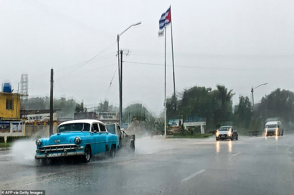 Cars traverse flooding roads in Cuba on Friday as Hurricane Ida passes through