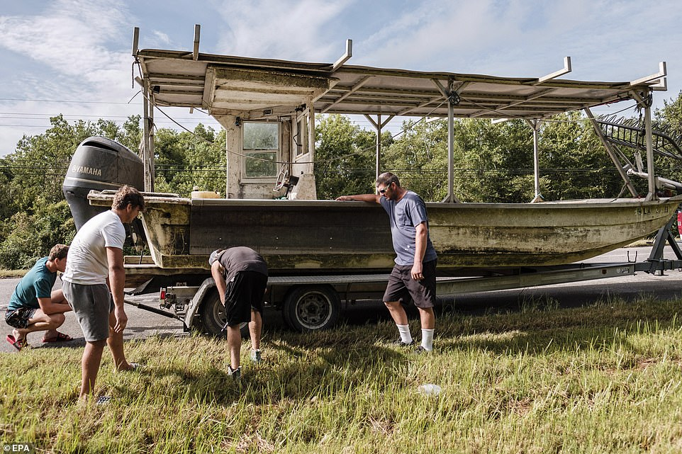 Evacuees from New Orleans' Charles Parish change a tire on their boat trailer on August 28 as they race to get out of impending Hurricane Ida's path