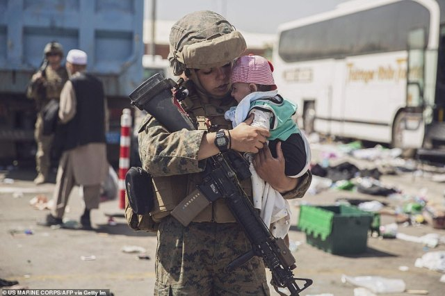 An US Marine with the 24th Marine Expeditionary Unit carrying a baby as the family processes through the Evacuation Control Center