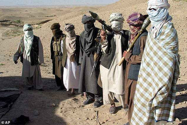 Taliban militants pose with weapons at a location south of Kabul
