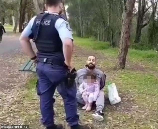 The officers called his daughter over to go back to her dad after he refused to co-operate, with the toddler walking over and sitting down in her father's lap