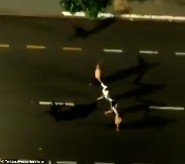 A line of hostages (right) is marched through the street by two gunmen wearing black (visible centre left and top) during the overnight raid in Brazil