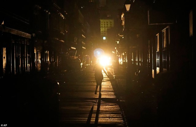 A police officer patrols past woman walking along Bourbon Street in the French Quarter. Anyone in need of emergency help was asked to go to their local patrol officer or go to their nearest fire station