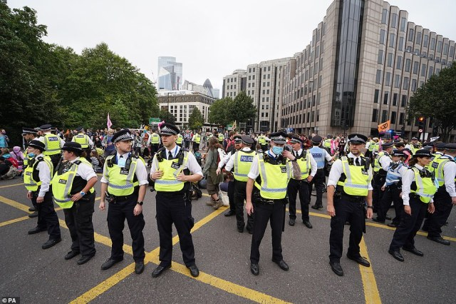 Police and members of Extinction Rebellion at Tower Hill during their march in central London this afternoon