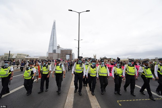 Large numbers of police officers accompanied one of the groups of activists as they crossed London Bridge today